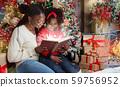 Beautiful black mom reading book to daughter near Christmas tree. 59756952