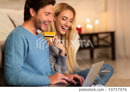 Cheerful Couple Making Online Order Sitting On Floor Indoor 59757976