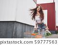 young happy women having fun shopping trolley race outdoors. 59777563