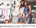 Young women have fun with a supermarket basket in the evening. Attractive young woman spend time 59777745