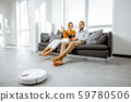 Young couple relaxing while automatic vacuum cleaner working at home 59780506