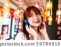 Happy girl listens to music on headphones in cafe 59784916