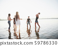 Young smiling friends play beach volleyball on the lake in the afternoon. 59786330
