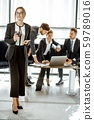 Portrait of a business woman with team indoors 59789016