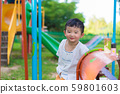 Young Asian boy play a iron train swinging at the 59801603