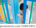 Sad Asian kid behind the grid trying to escape. 59803801