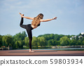 Young woman practicing yoga at city lake 59803934