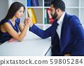 Man and woman doing arm wrestling in office 59805284