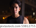 Portrait of young handsome Asian man outdoors at night 59812755