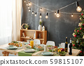 Festive table served for Christmas party with lamps hanging over meal 59815107