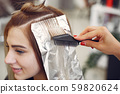 Hairdresser colored hair her client in a hair salon 59820624