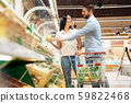 Daily Shopping. Couple in the supermarket with cart together buying vegetables looking at each other 59822468