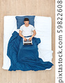 Bedtime. Guy lying on bed under blanket top view chatting on laptop smiling happy 59822608