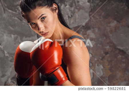 Boxing. Woman boxer in gloves standing isolated on wall protective confident close-up 59822681