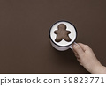 Holding a cup of milk and a gingerbread cookie. 59823771