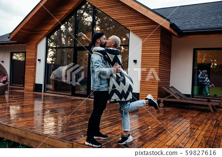 Attractive family of wife and husband kissing next to big wooden house 59827616