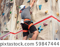 Sporty man practicing indoor rock climbing in climbing gym. 59847444