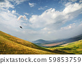 A paraglider flies in the sky in a cocoon suit on a paraglider over the Caucasian countryside with 59853759