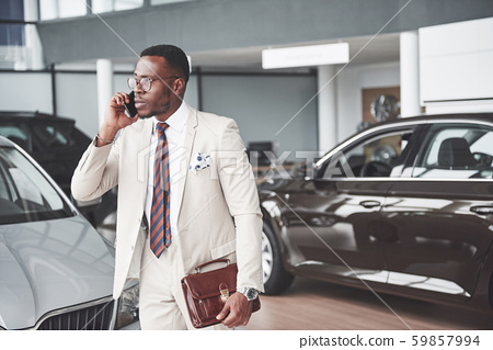 Young black businessman on auto salon background. Car sale and rent concept 59857994