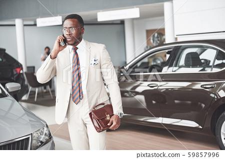 Young black businessman on auto salon background. Car sale and rent concept 59857996