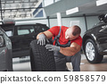 Mechanic holding a tire tire at the repair garage. replacement of winter and summer tires 59858579