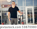 Handsome man standing in a airport 59870980