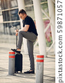 Handsome man standing in a airport 59871057