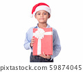 Asian Little boy wearing Santa Claus cap and holding red gift box over white background. 59874045