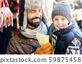 Father and son eating sweets on Christmas Market 59875458