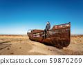 Man sits on boat in desert in Aral sea, Kazakhstan 59876269