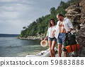 Cute young and couple on river background. A guy and a girl with backpacks are traveling by boat 59883888