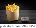French fries in a paper basket. Fast food.French fries in a paper box on black background 59892454