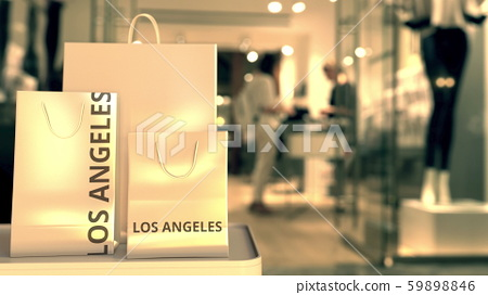 Paper shopping bags with Los Angeles caption against blurred store entrance. Retail in the United 59898846