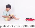 cute little boy play semi-automatic toy car on 59905908