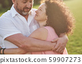 A loving, handsome senior couple outdoors in the park, many years together 59907273