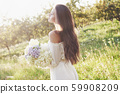 A beautiful young girl in a white light dress and a bouquet of summer flowers lays a fine day in the 59908209