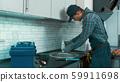 Working on it. Plumber installing sink siphon 59911698