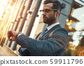 What time is it Young and handsome bearded businessman in eyeglasses checking the time while 59911796