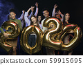 New 2020 year is coming. Group of happy multiethnic people holding gold colored numbers and looking 59915695