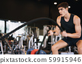 Caucasian young man doing exercises with battle rope strength and motivation in the gym 59915946