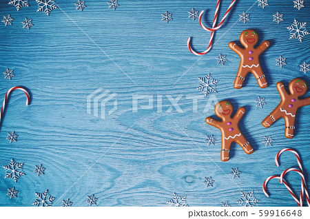 Christmas background. Gingerbread man, Christmas candy cane and snowflakes on blue wooden background with copy space for text, 3D rendering 59916648