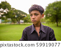 Portrait of young Indian boy relaxing at the park 59919077