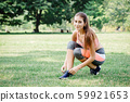 Beautiful sport exercise fit girl tie her shoe at outdoor green park. 59921653