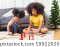 two black girl daughter kids playing train model together at living room. 59922030