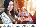 Business girl smiling with shopping cart in her hand for online buy and sale concept 59922507