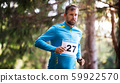 Front view of young man running a race competition in nature. 59922570