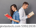 Relationship Concept. Young couple studio standing back to back isolated on grey reading books 59922636