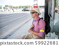 Senior blind man with white cane waiting for public transport in city. 59922681