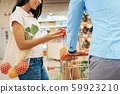 Young adult couple choosing fresh vegetables in grocery 59923210