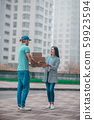 Delivery man giving boxes to woman while meeting her in the street 59923594